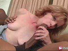 Slutty chick wraps her lips around two enormous black dicks.